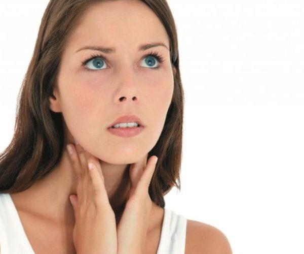 Женщина трогает щитовидную железу
