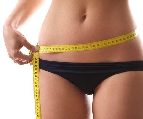 Женщина измеряет талию